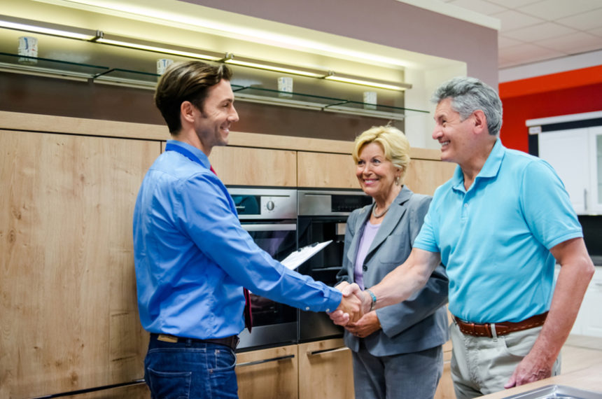 A senior couple buying a new kitchen in a modern appliance store. They finalizing their contract by a handshake with the young and smart sales clerk. Horizontal indoor shot.