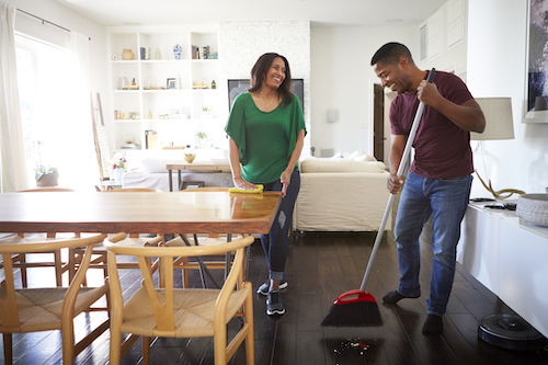 Man sweeping the floor. Woman wiping the dinning table.