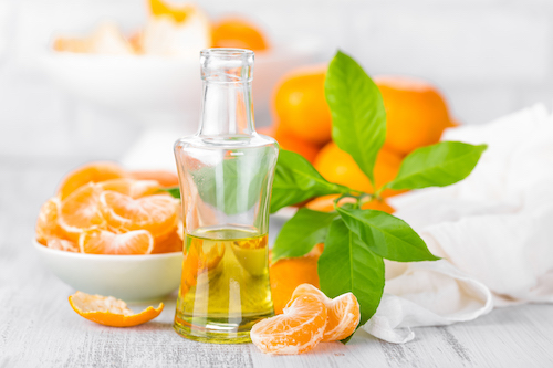 Tangerines with leaves and bottle of essential citrus oil on a white table